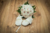 Shoes and bouquet on a wooden floor — Stock Photo
