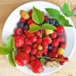 Stock Photo: Berries on a plate on a wooden board