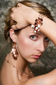 Elegant woman and gold jewelry — Stock Photo
