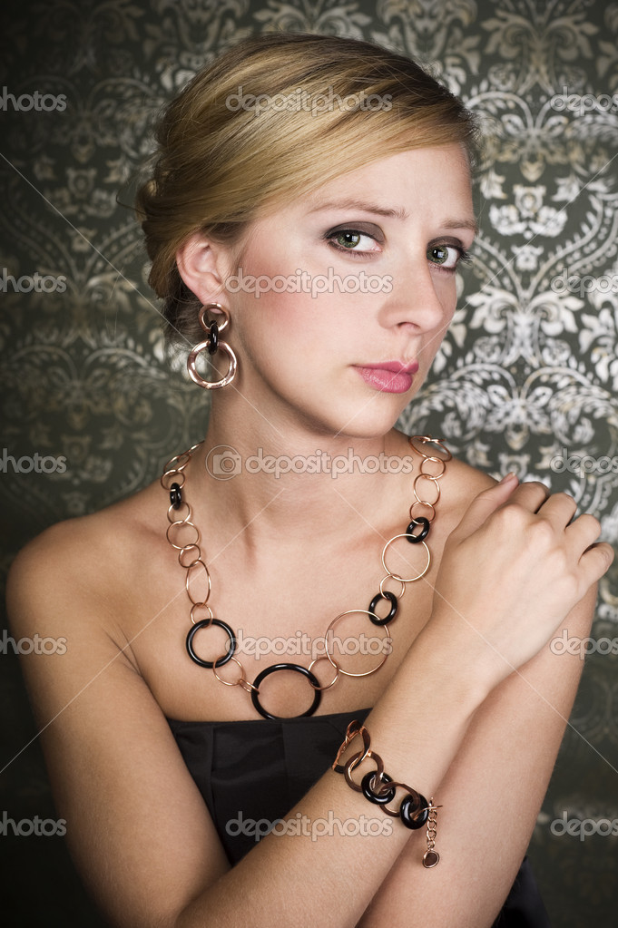 Elegant woman wearing golden necklace and earring, over wallpaper background  Stock Photo #6866749