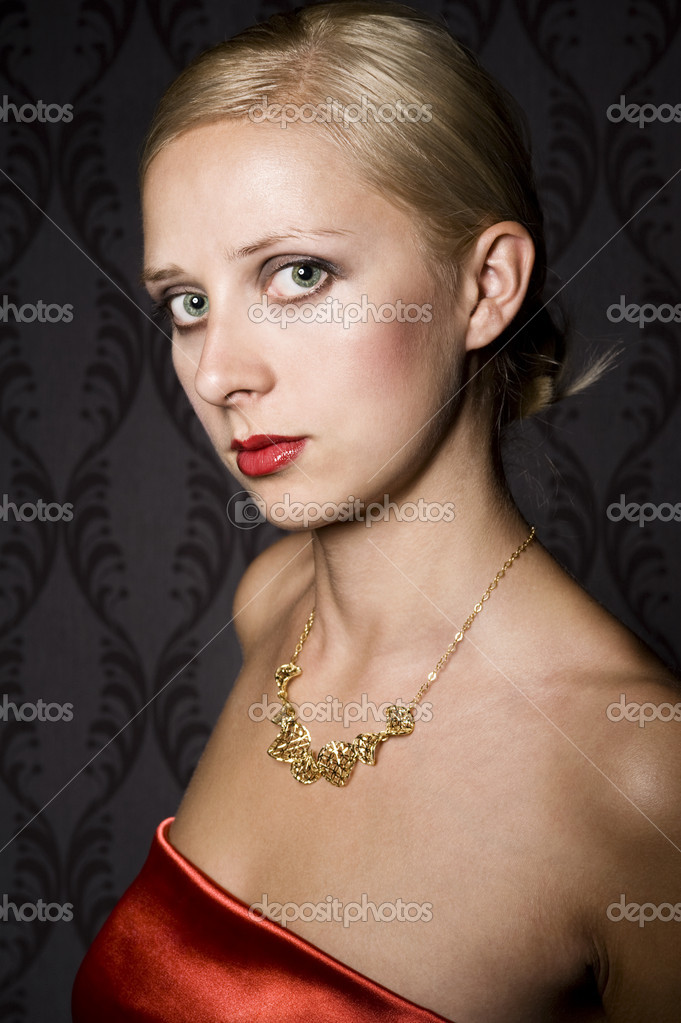 Elegant blonde woman wearing golden necklace, over wallpaper background — Stock Photo #6866878