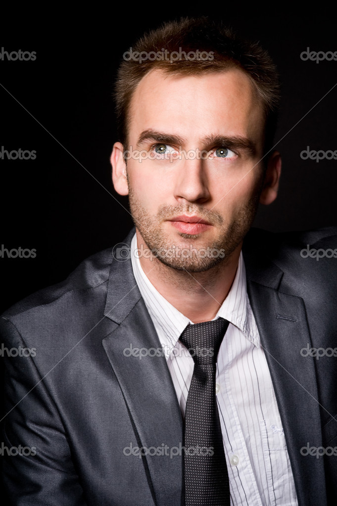 Portrait of ypung handsome businessman over black background — Stock Photo #6867107