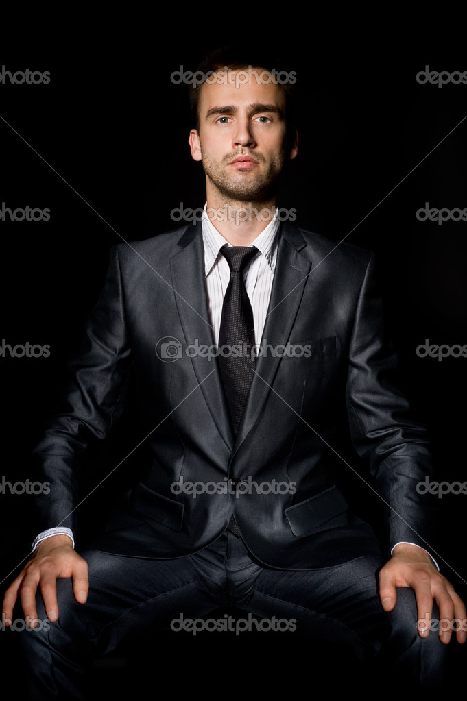 Young confident businessman with hands on his knees — Stock Photo #6867119