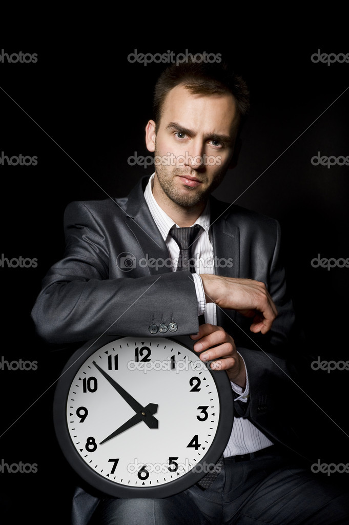 Young handsome businessman holding big clock — Stock Photo #6867162