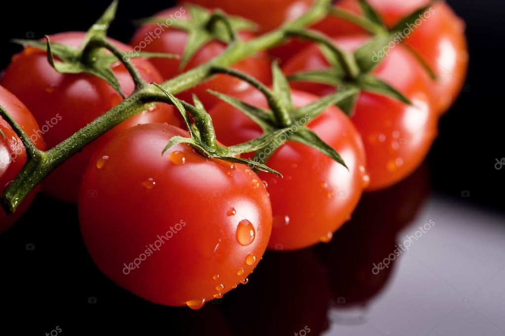 Fresh and wet tomatoes on the black table — Stock Photo #6874652