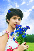 Beautiful girl with a bouquet of cornflowers — Stock Photo
