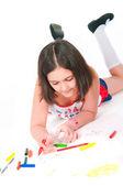 The girl lying draws white background — Stock Photo