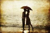 Par kyssar på stranden i solnedgången. — Stockfoto