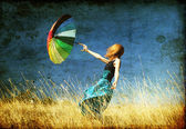 Redhead girl with umbrella at windy grass meadow. — Stock Photo