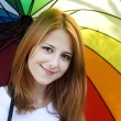 Red-haired girl with umbrella in autumn season — Stock Photo