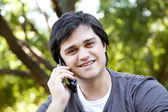 Vacker brunett män ringer genom mobil på utomhus. — Stockfoto