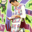 Style boy with laptop near graffiti wall. - Zdjęcie stockowe