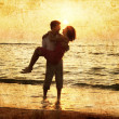 Couple at the beach in sunset. — Stock Photo