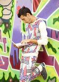 Style boy with laptop near graffiti wall. — Stock Photo