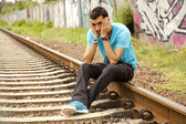 Young boy sitting at railway — Stock Photo