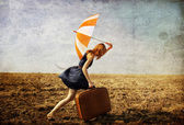 Lonely girl with suitcase and umbrella at countryside field. — Stock Photo
