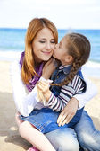 Two sisters 5 and 22 years old at the beach in sunny autumn day — Stock Photo