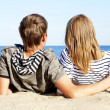 Happy pair of male and female on coast behind blue sea — Stock Photo