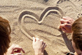 drawing heart at sand — Stok fotoğraf