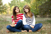Portrait of redhead and brunette girls at outdoor. — Stock Photo