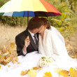 Couple sitting at the park with umbrella — Stock Photo
