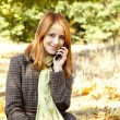 Red-haired girl calling by the phone in the autumn park. — Stock Photo #7317164