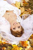 Beautiful bride liying down in the park. — Stock Photo
