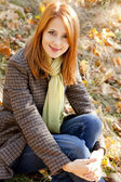 Portrait of red-haired girl in the autumn park — Stock Photo