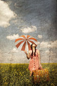 Brunette enchantress with umbrella and suitcase — Stock Photo