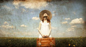 Lonely girl with suitcase at country. — Stock Photo