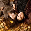 Couple lying in the park in fall — Stock Photo