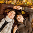 Couple lying in the park in fall — Stock Photo #7413144