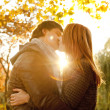Couple kissing in the park at sunset — Stock Photo
