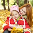 Mother and daughter in autumn yellow park - Stock Photo