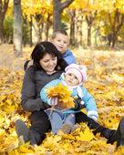 Madre y sus niños están jugando en el parque otoño. — Foto de Stock