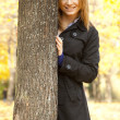 Smiling happy girl in autumn park - Stock Photo