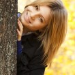 Stock Photo: Smiling happy girl in autumn park