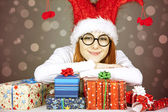 Girl in christmas cap and glasses with gift boxes. — Stock Photo