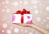 En låda bundna med en röd satin band rosett. — Stockfoto