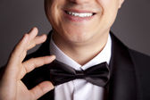 A close-up shot of a man straightening his tux. — Stock Photo