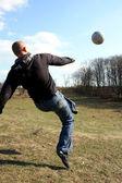 Der mann spielt mit fußball in holz natur — Stockfoto
