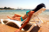 The woman in a bathing suit which has a rest lying on an armchai — Stock Photo