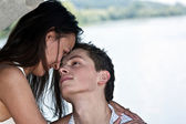 Beautiful man and the woman kiss ashore at the river under the — Stock Photo