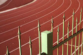 Fence against a red racetrack — Stock Photo