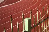 Recinzione contro una pista rossa — Foto Stock