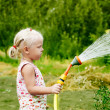 Little girl watering the grass in the garden — Stock Photo
