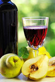 Glass of red wine and quince fruits. — Stock Photo