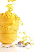 Pila de platos amarillos y dorados copos de maíz cae en el bowl — Foto de Stock