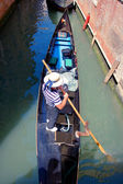 Venice, italy. gondolier driving his gondola though narrow canal — Stock Photo