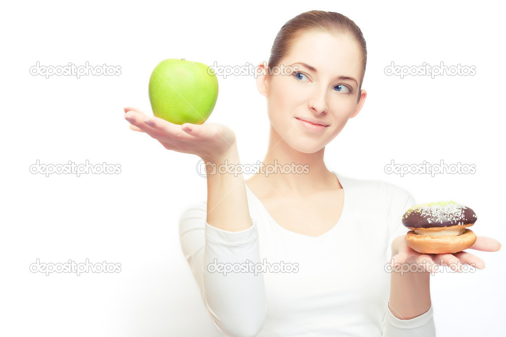 Portrait of young cheerful woman choosing between apple and cake, over white, with some shadows left — Stock Photo #6960506